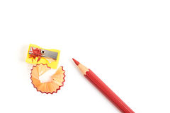 Le rouge a coloré le crayon avec l'affûteuse d'isolement sur le fond blanc Image libre de droits