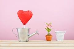 Le rouge a déjoué le bâton de coeur de chocolat avec la petite boîte d'arrosage argentée photographie stock
