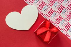 Le rouge de backround de jour de valentines gify la boîte avec le fond de ruban et amour rouges de lettrage Photographie stock