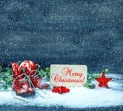 Le rouge de décoration de Noël se tient le premier rôle et les chaussures de bébé antiques dans la neige Photo libre de droits