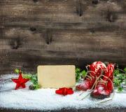 Le rouge de décoration de Noël tient le premier rôle la carte postale antique de neige de chaussures de bébé Photographie stock libre de droits