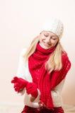 Le rouge de port de femme assez heureuse a tricoté l'écharpe et les gants Photographie stock libre de droits