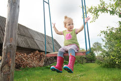 Le rouge de port de fille heureuse d'enfant en bas âge badine des bottes de caoutchouc montant sur l'oscillation rustique faite m Image libre de droits