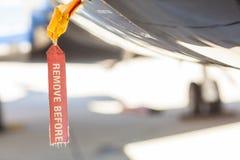 Le rouge enlèvent avant étiquette de vol sur un fuselage d'avion Images libres de droits