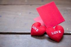 le rouge enveloppent avec l'oreiller de coeur de forme sur l'amour des textes Photo stock