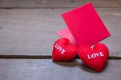 le rouge enveloppent avec l'oreiller de coeur de forme sur l'amour des textes et sur en bois Image stock