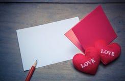le rouge enveloppent avec l'oreiller de coeur de forme sur l'amour des textes, feuille de papier Photographie stock