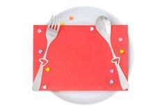 Le rouge enveloppent avec la fourchette et la cuillère en forme de coeur sur le pla blanc Image libre de droits