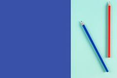 Le rouge et le bleu ont coloré des crayons sur le fond bleu de couleur Photos stock