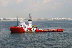 Le rouge et le blanc tirent le bateau avec effort dans l'ancrage de Singapour. photos libres de droits