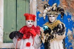 Rouge et couples masqués par noir Photos stock