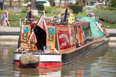 Le rouge et le vert brillamment colorés dévastent le bateau de canal de newell et de fils se reflétant dans l'eau Photographie stock