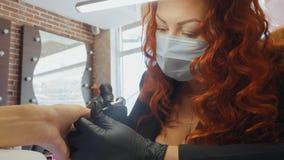 Le rouge femelle fait une procédure de station thermale pour les ongles du client Photo libre de droits