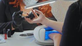Le rouge femelle fait une procédure de station thermale pour les ongles du client Photos stock