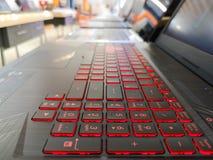 Le rouge a mené le clavier léger, paning Ordinateur portable avec le contre-jour rouge, choisissant un ordinateur portable, ordin photo stock