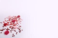 Le rouge mignon a dispersé des coeurs de paillette avec des fleurs de tissu sur un fond blanc Images stock