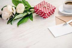 Le rouge a pointillé le boîte-cadeau, l'enveloppe de papier d'emballage et la carte de voeux, la tasse de café et le bouquet vide Image libre de droits