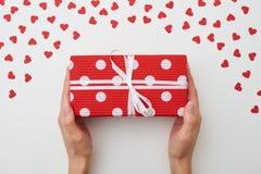 Le rouge a pointillé le long boîte-cadeau avec le ruban blanc sur le fond blanc Photo stock