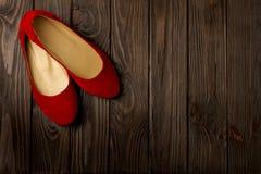 Le ` rouge s de femmes chausse des ballerines sur le fond en bois Photos libres de droits
