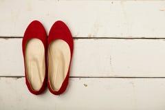 Le ` rouge s de femmes chausse des ballerines sur le fond en bois Photographie stock