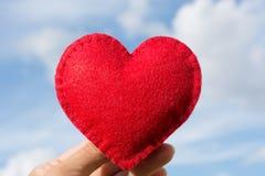 Le rouge a senti la forme de coeur dans la main sur le ciel bleu avec des nuages comme fond Carte du `s de Valentine Images libres de droits