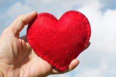 Le rouge a senti la forme de coeur dans la main sur le ciel bleu avec des nuages comme fond Carte du `s de Valentine Image libre de droits