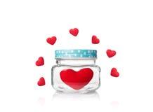 Le rouge a senti le coeur dans le pot en verre avec le couvercle bleu de point de poka Image libre de droits