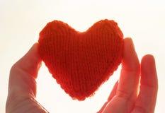 Le rouge a tricoté le coeur gardant mes doigts sur le fond d'ensoleillé photographie stock libre de droits