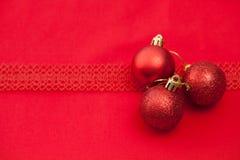 Le rouge a tricoté des boules de Noël avec le ruban sur un tissu rouge Image libre de droits