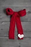 Le rouge a tricoté l'arc avec le coeur blanc sur le fond en bois pour le Christ Image libre de droits