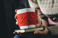 Le rouge a tricoté la tasse de laine avec le modèle de coeur dans des mains femelles Images stock