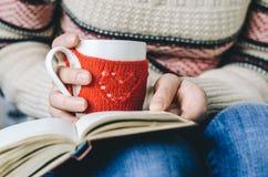 Le rouge a tricoté la tasse de laine avec le modèle de coeur dans des mains femelles Image stock