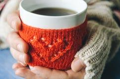 Le rouge a tricoté la tasse de laine avec le modèle de coeur dans des mains femelles Photographie stock libre de droits