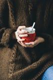 Le rouge a tricoté la tasse de laine avec le modèle de coeur dans des mains femelles Photo libre de droits
