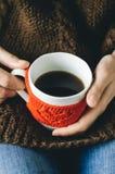 Le rouge a tricoté la tasse de laine avec le modèle de coeur dans des mains femelles Photographie stock