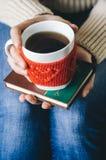 Le rouge a tricoté la tasse de laine avec le modèle de coeur dans des mains femelles Photo stock