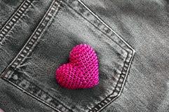 Le rouge a tricoté le coeur dans la poche arrière de jeans Image libre de droits