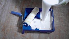 Le rouleau de peinture se situe dans le plateau bleu sur un plancher dans un colorant plat et blanc découle du seau, des outils e banque de vidéos
