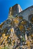 Le rovine della torre di un castello medievale su una roccia immagini stock
