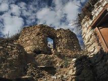 Le rovine di vecchia casa tibetana, muratura su un'alta collina con un'apertura vuota della finestra contro un fondo del cielo bl Fotografia Stock Libera da Diritti