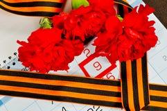 Le ruban de St George et les oeillets rouges au-dessus du calendrier avec le 9 mai datent Image stock
