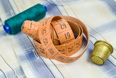 Le ruban métrique du ` s de tailleur avec un dé et une bobine de fil sur un fond de tissu Image stock