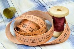 Le ruban métrique du ` s de tailleur, une bobine en bois de fil et dé sur le tissu Image libre de droits