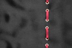 Le ruban rouge sont insérés dans un satin onduleux noir Beau fond à la mode Photographie stock