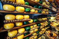 Le ruote del formaggio verdi ed i colori gialli sugli scaffali di legno alla caseificazione comperano Fotografia Stock