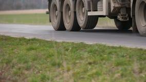 Le ruote della gomma del camion filano, si chiudono su, incandescenza in sole di sera mentre l'impianto di perforazione guida lis archivi video