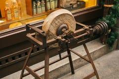 Le ruote di pietra antiche sulle strutture di legno all'entrata al deposito con il Natale hanno decorato la vetrina decorativo Fotografia Stock