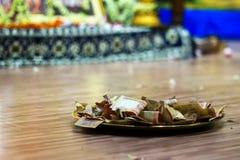 Le rupie indiane si sono raccolte su un piatto come offrendo a Dio indù fotografia stock