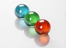 Le RVB colorent les boules/marbres /Orbs sur le fond réfléchi blanc Photo stock
