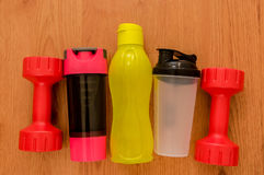 Le ` s d'athlète a placé avec deux haltères roses, et trois bouteilles de l'eau, dans une rangée sur le fond en bois Image libre de droits